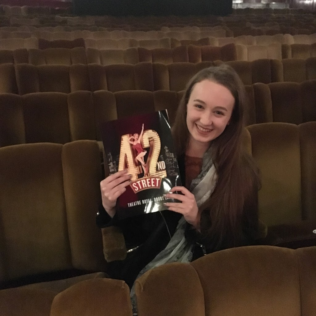 girl sitting in theatre holding 42nd street programme