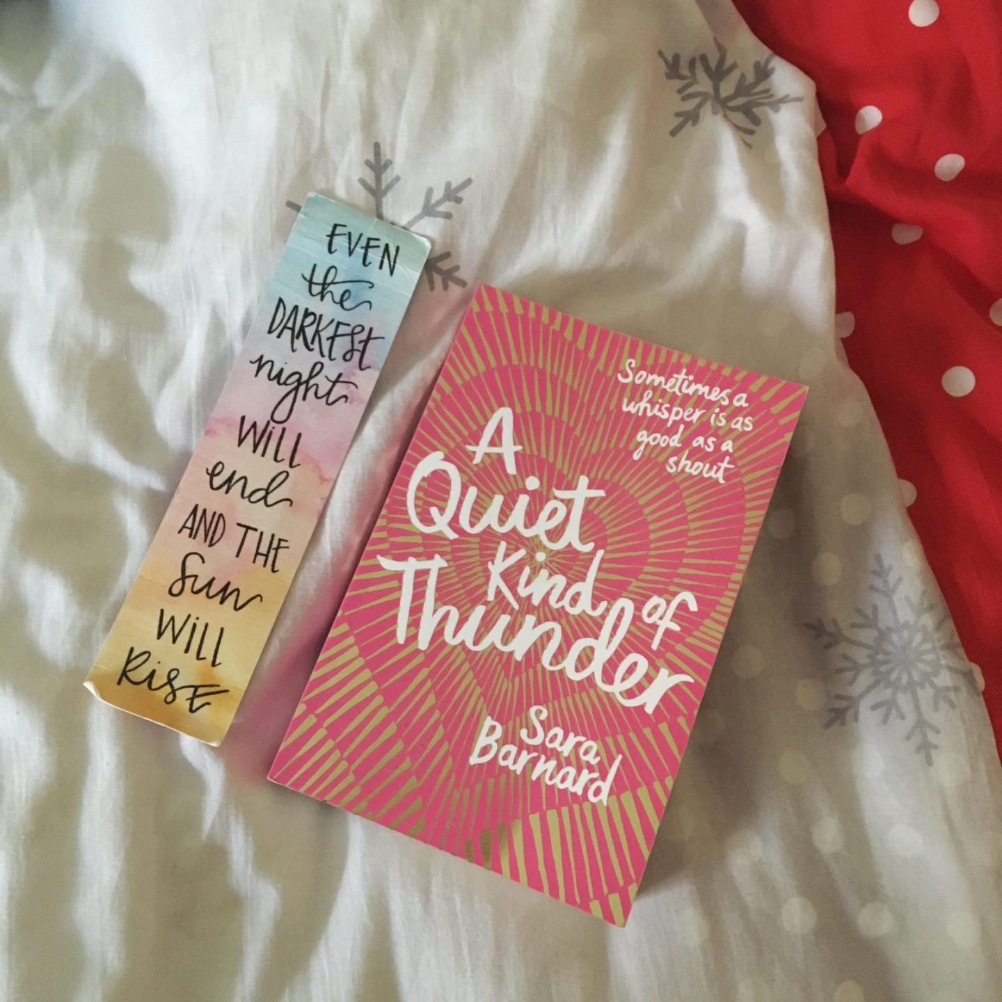 pink book on bedsheets, next to bookmark