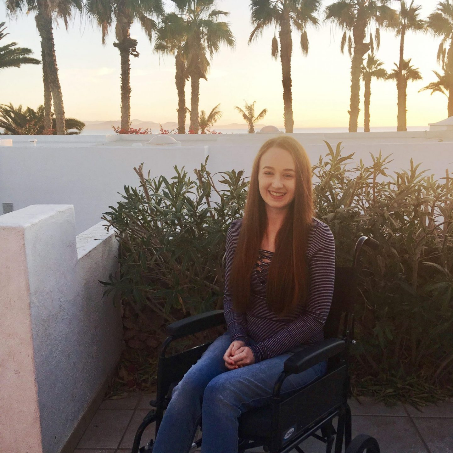girl in jeans and t-shirt in wheelchair on an outdoor balcony
