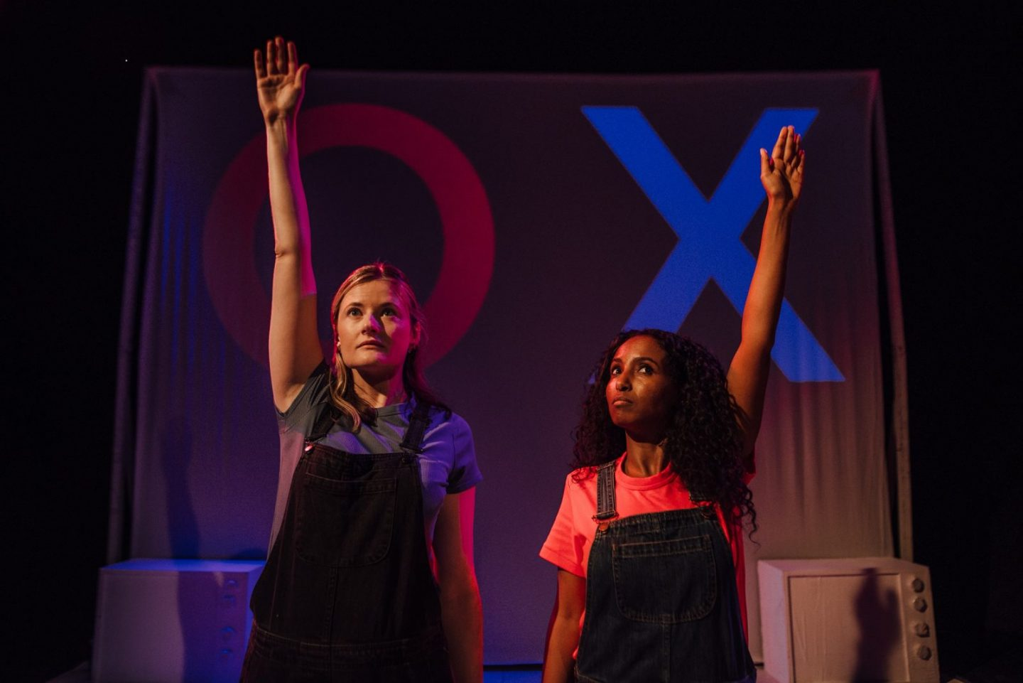 On stage photo of two women stood up with one hand raised in the air: one woman looks confident and the other more uncertain