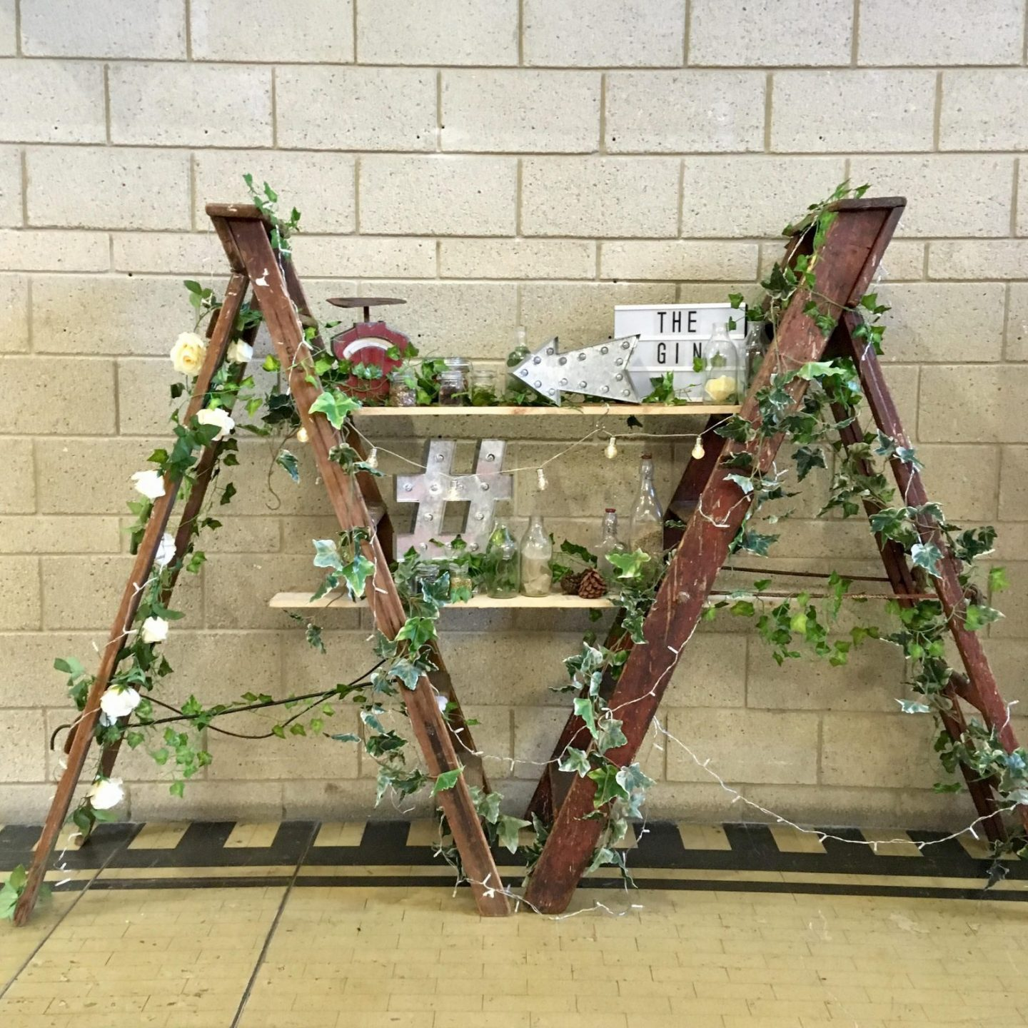 floral display of ladders wrapped in flowers, light boards and gin bottles