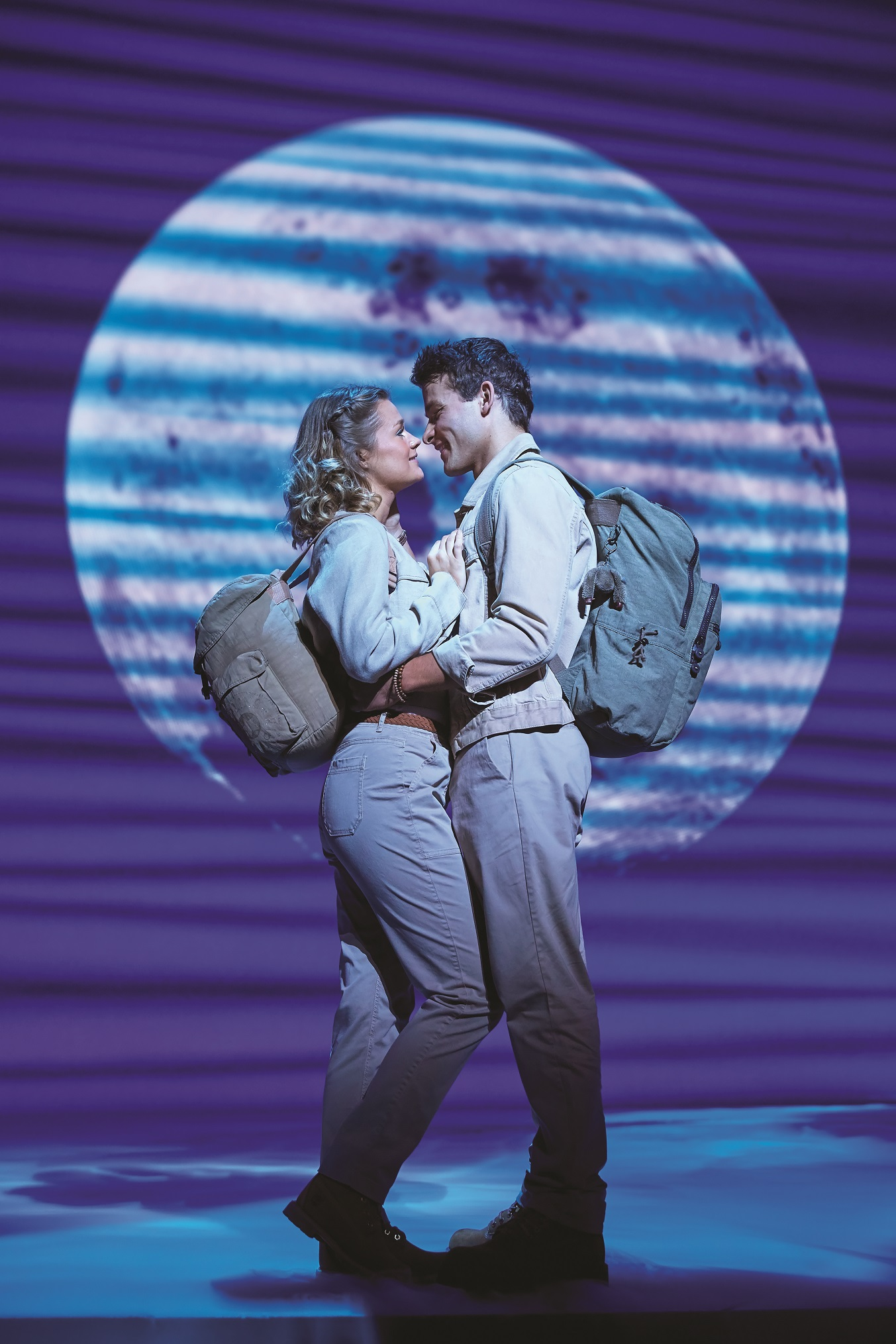 onstage photo of couple wearing travel gear embracing, lit by moonlight scenery