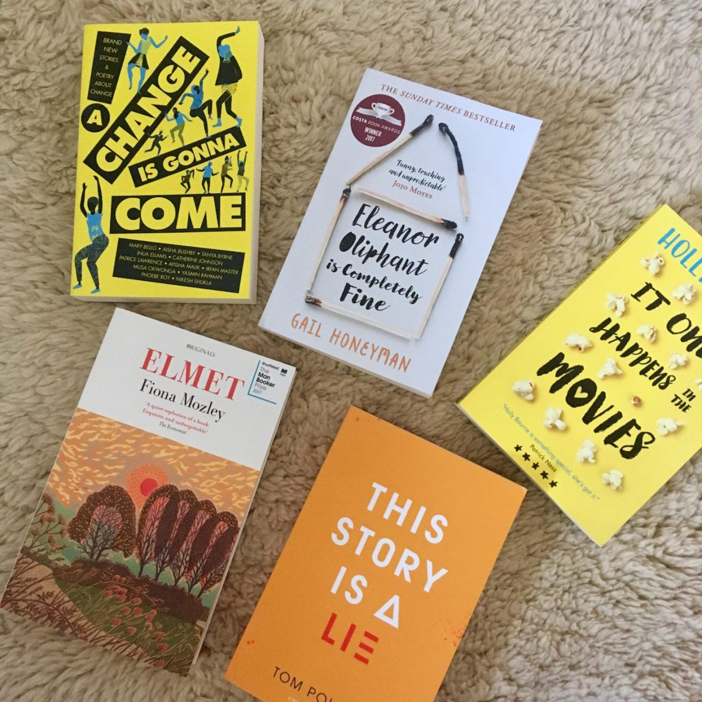 five paperback books arranged on neutral carpet background