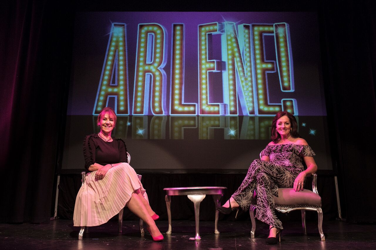 two women sat on chairs on a stage in front of a backdrop reading 'arlene'