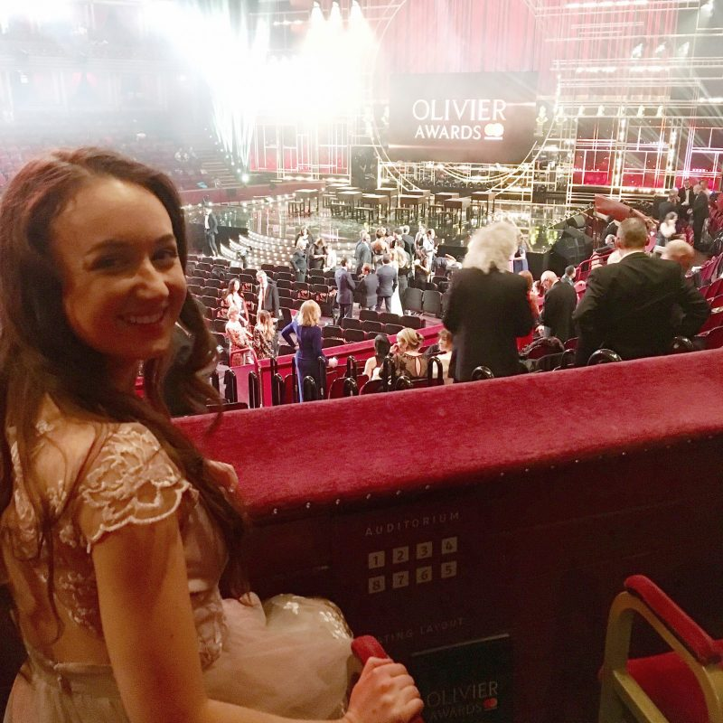 girl wearing pink dress sat in a seat overlooking the stage, looking over shoulder and smiling