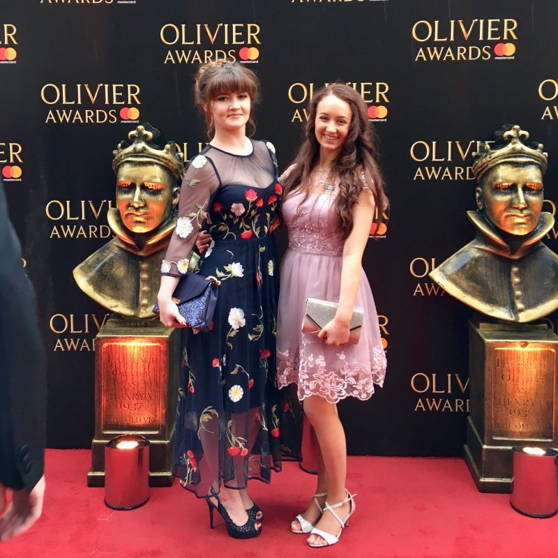 full length image of two girl in formal wear, standing on red carpet and smiling at camera
