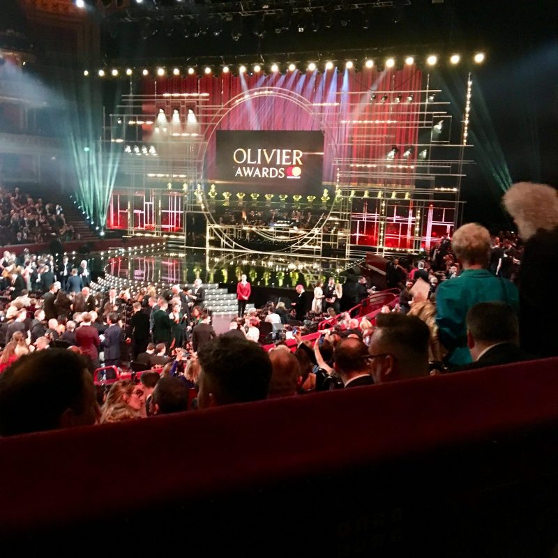 inside the royal Albert hall pre-show, featuring audience and a stage with big 'olivier awards' logo in the background