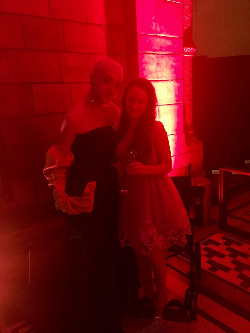 full length photo of pippa stood next to jamie campbell, lit by red lighting