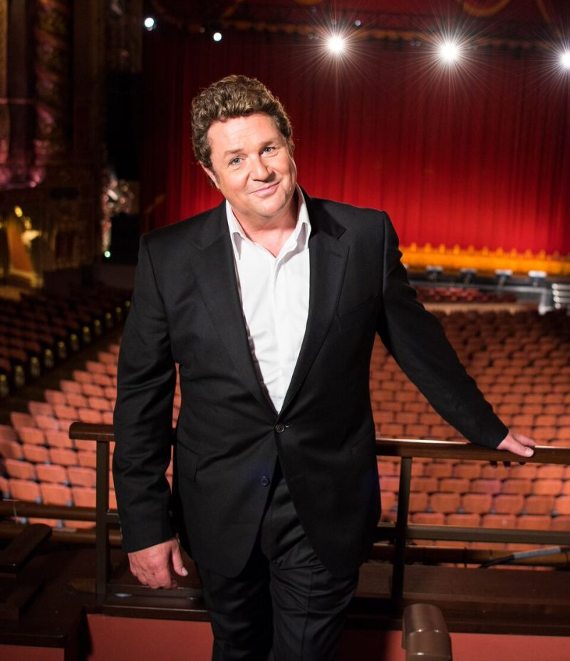 michael ball standing in front of a theatre auditorium, with red curtains in background