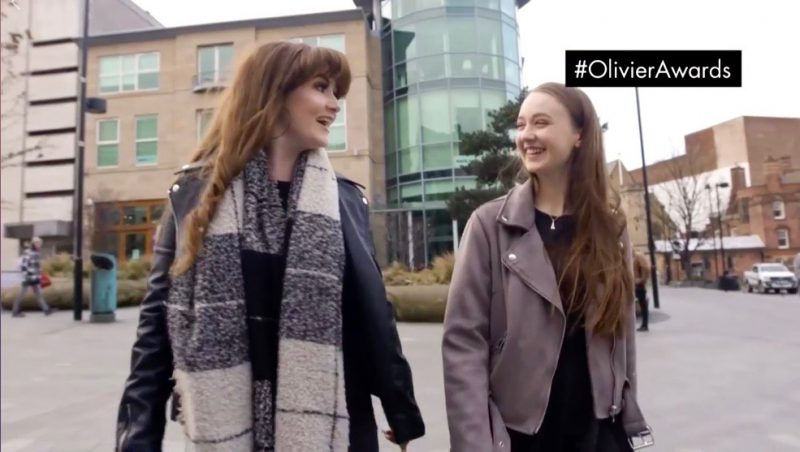 screenshot from promotional video of two girls walking outdoors whilst looking at each other and laughing