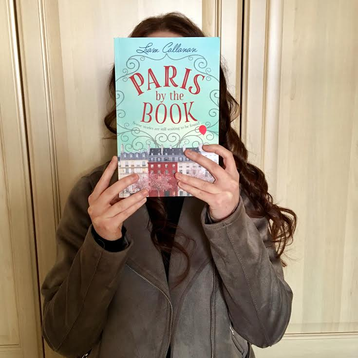 pippa wearing grey leather jacket, holding paris by the book cover in front of her face