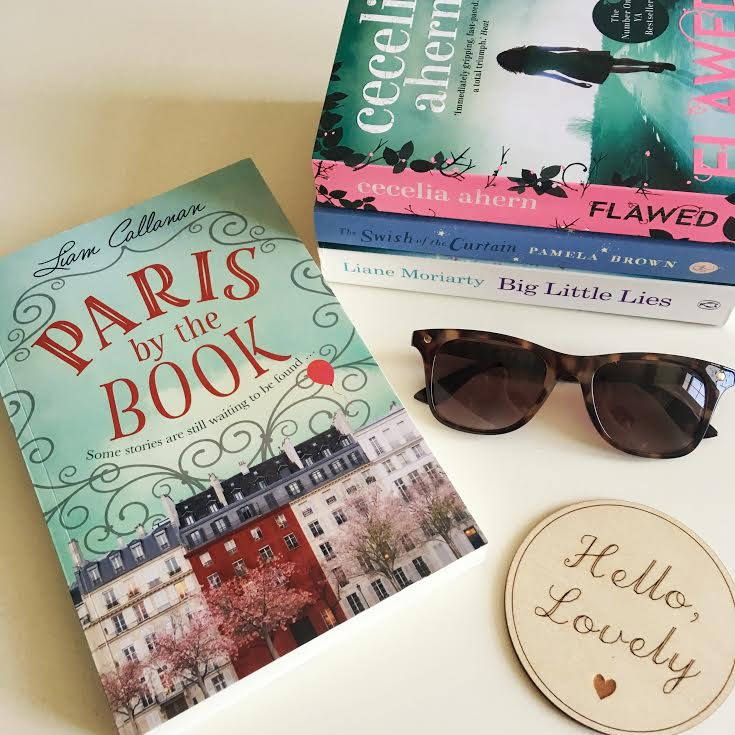 flatlay of four YA books on a white background, along with sunglasses and wooden coaster