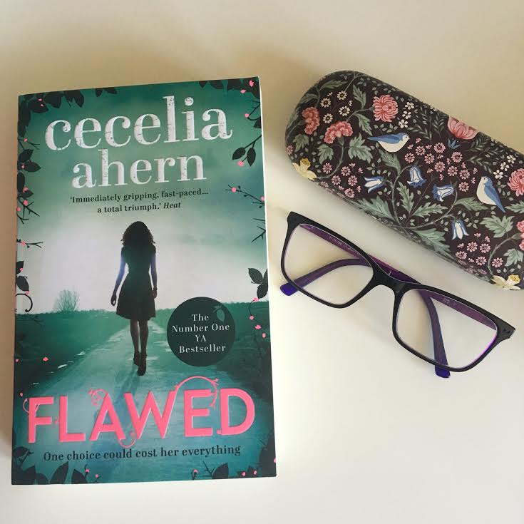 flawed book cover on white background along with purple glasses and flowery glasses case