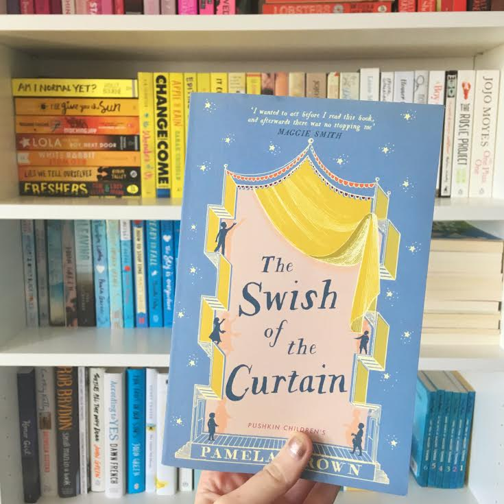 hand holding the swish of the curtain book, with rainbow bookshelves in background