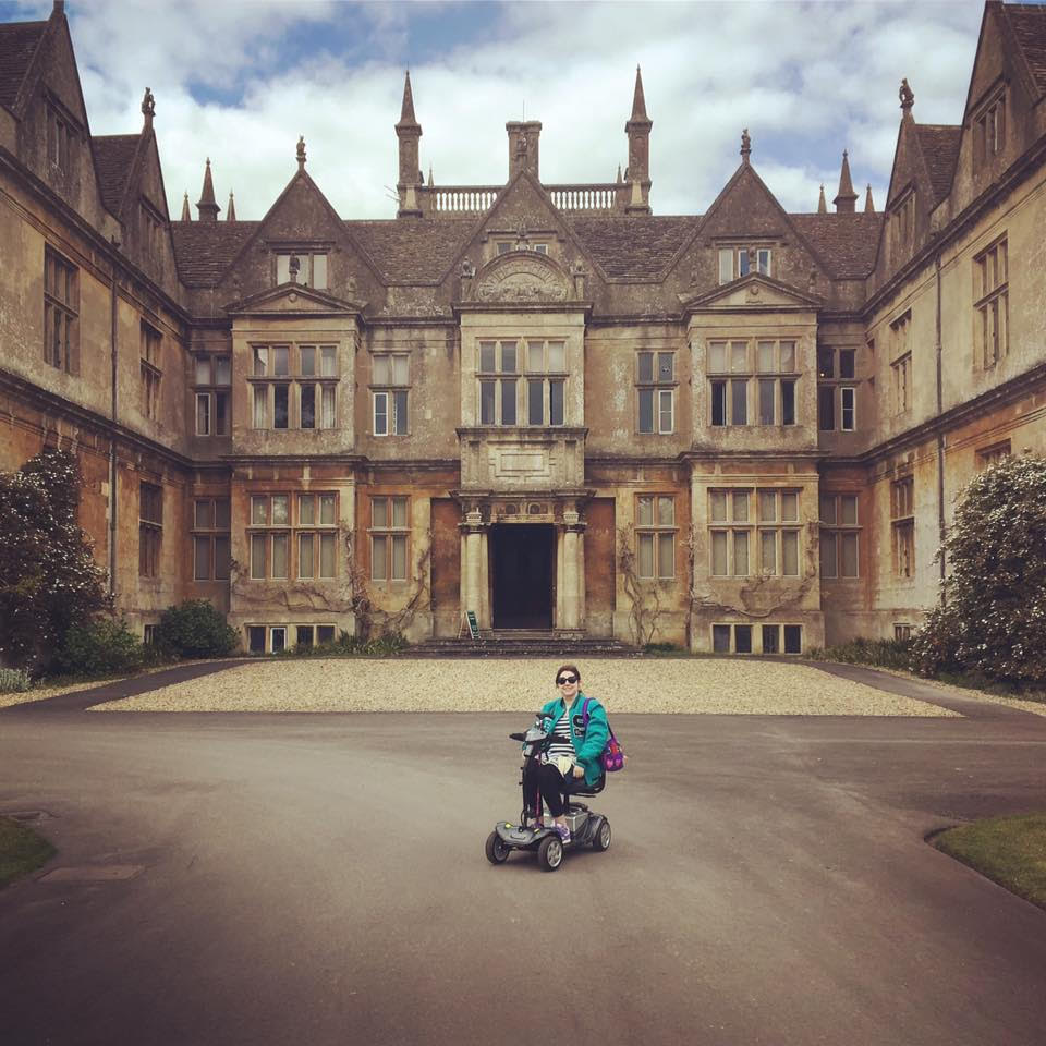 charlotte wearing a green jacket and sunglasses, on a mobility scooter in front of a large historic building
