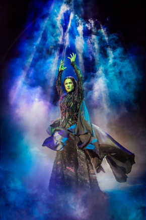 elphaba on broomstick elevated above stage with hands in air, surrounded by smoke and lights