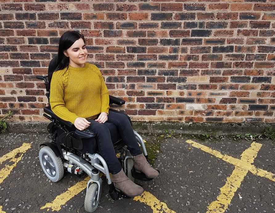 emma in powerchair wearing mustard knitted jumper, jeans and boots, in front of brick wall background