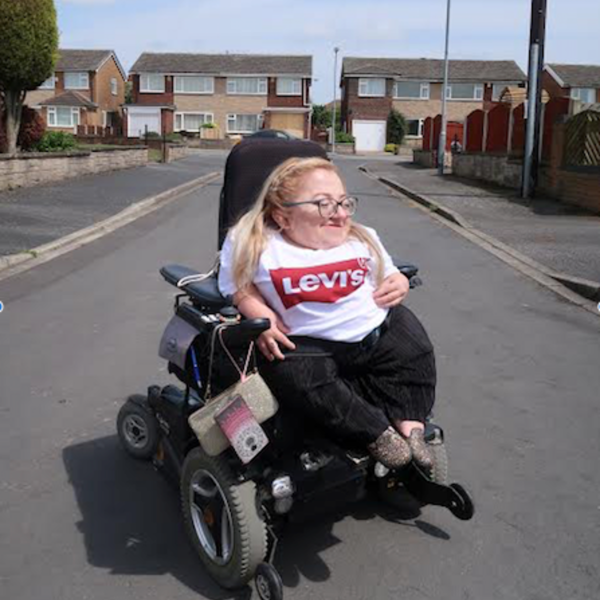 gem has blonde har and glasses, and is sat in powerchair smiling and looking to the right, wearing a levi's t-shirt. street roads and houses in background