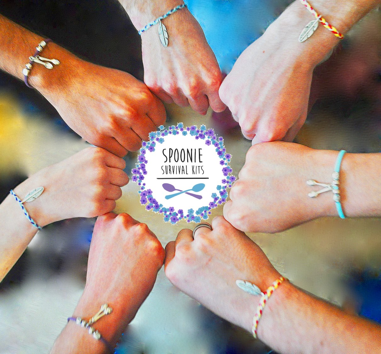 SSK logo surrounded by six hands meeting in the middle, all wearing SSK bracelets. image taken from above