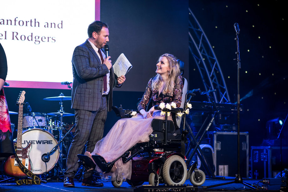 kate dressed formally in powerchair onstage, looking ay mad holding microphone who is presenting her with an award