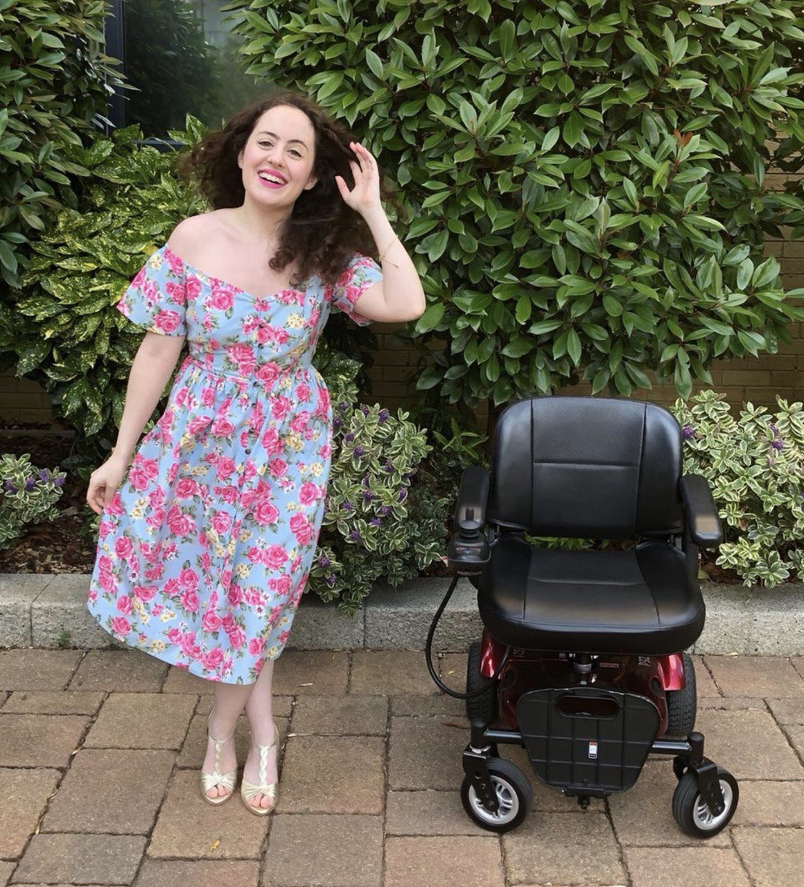 natasha stood next to powerchair, wearing pink flowery dress and laughing