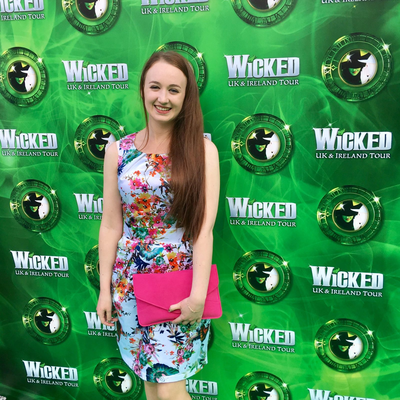 pippa standing in front of green wicked backdrop, wearing floral dress with pink clutch bag
