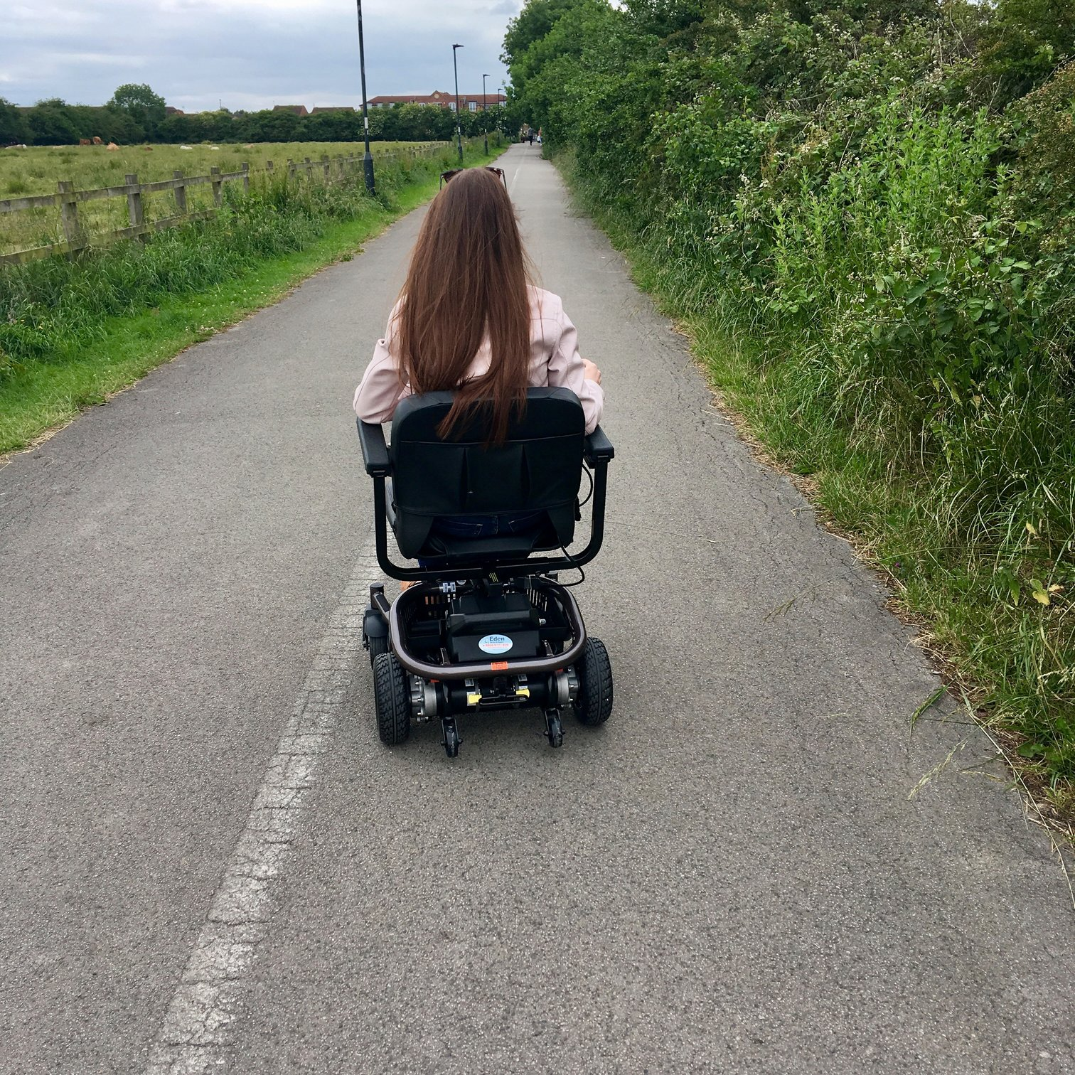 image taken from behind of pippa in powerchair travelling down country path