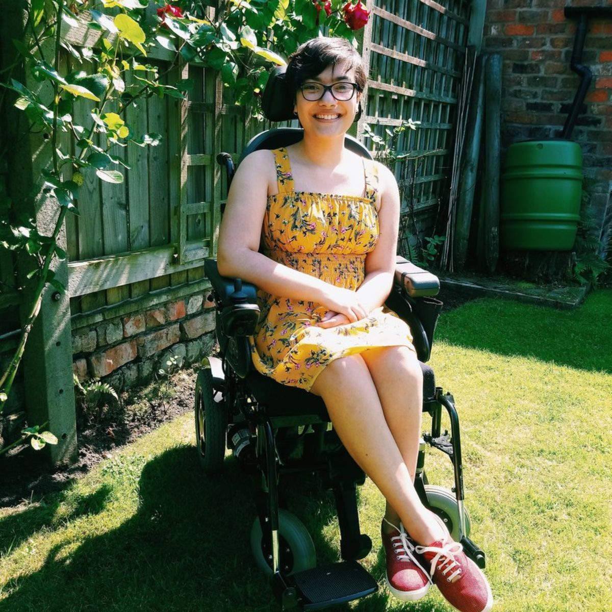 rosie has short hair and wears glasses. she's sat in her powerchair outside in the garden, wearing a yellow dress and red trainers