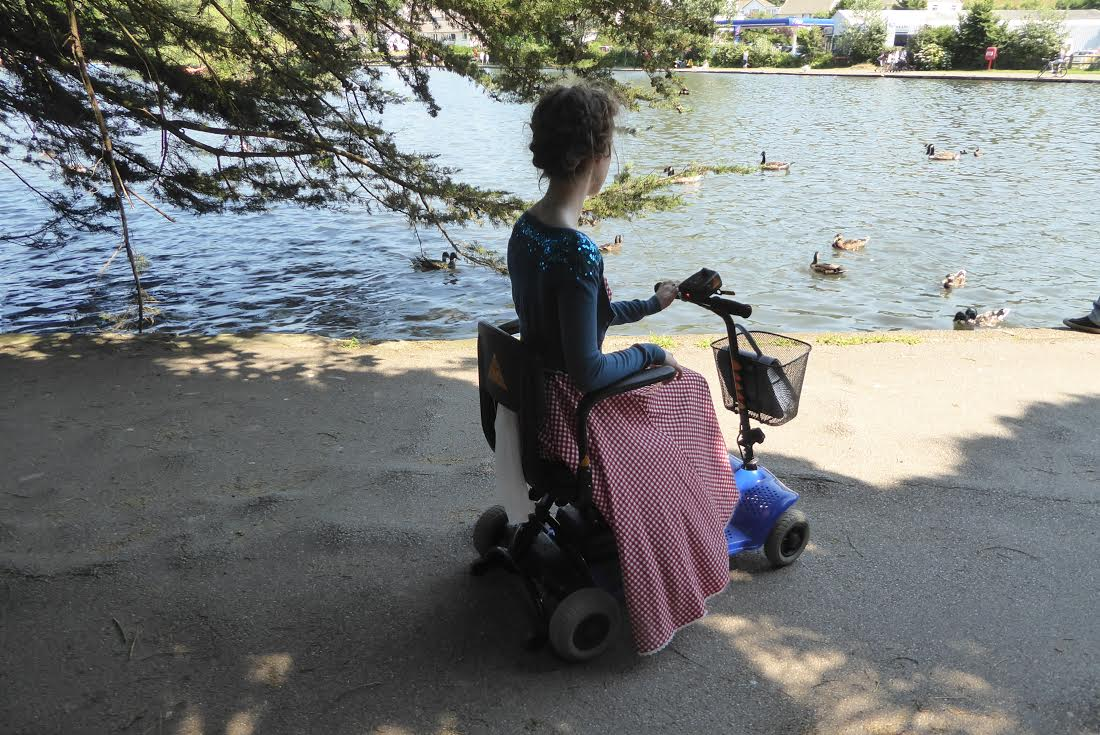sakara on scooter with blanket over knees and head turned away from camera, looking out over a blue lake