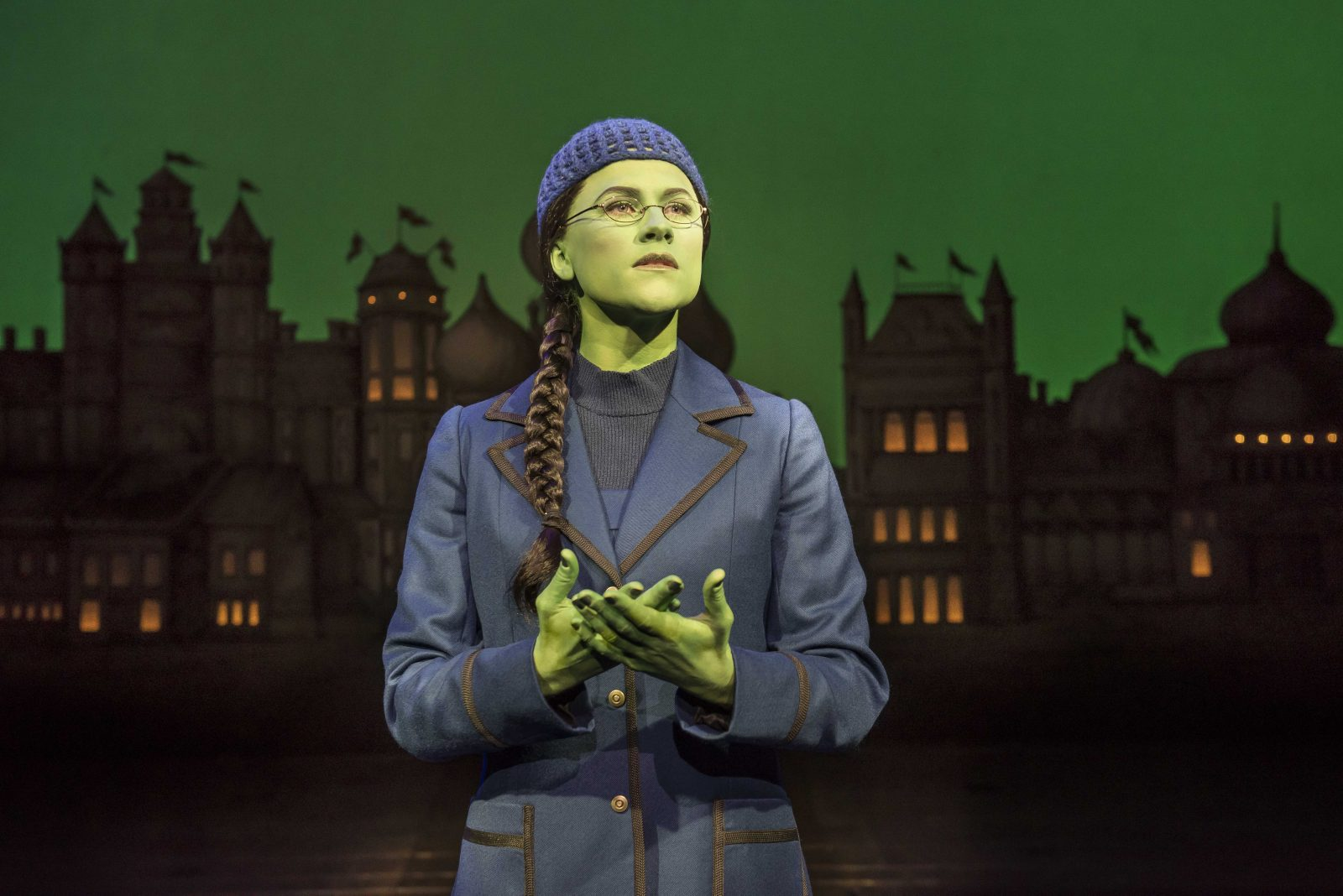 amy ross as elphaba, wearing all black and standing looking up at stage right with hands together