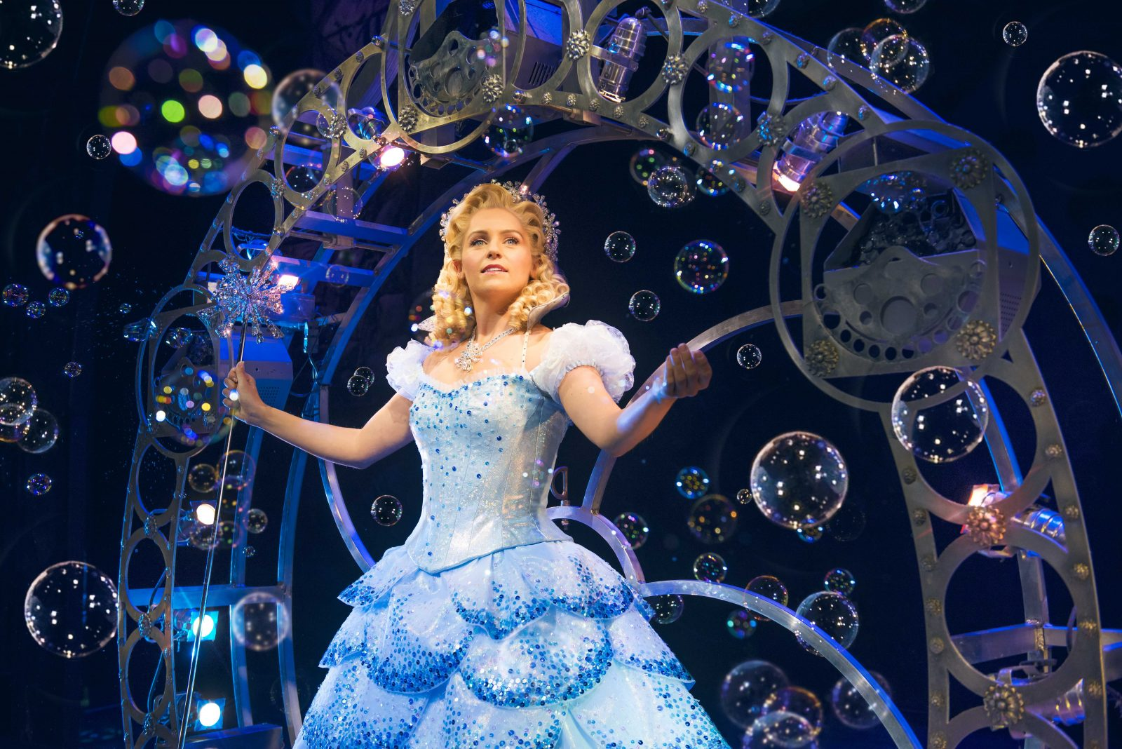 helen woolf as glinda, wearing a blue sparkly ballgown holding a wand, stood in her bubble
