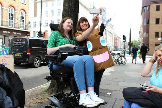 shona in powerchair wearing green top and jeans, taking selfie with lady dressed in poo emoji costume