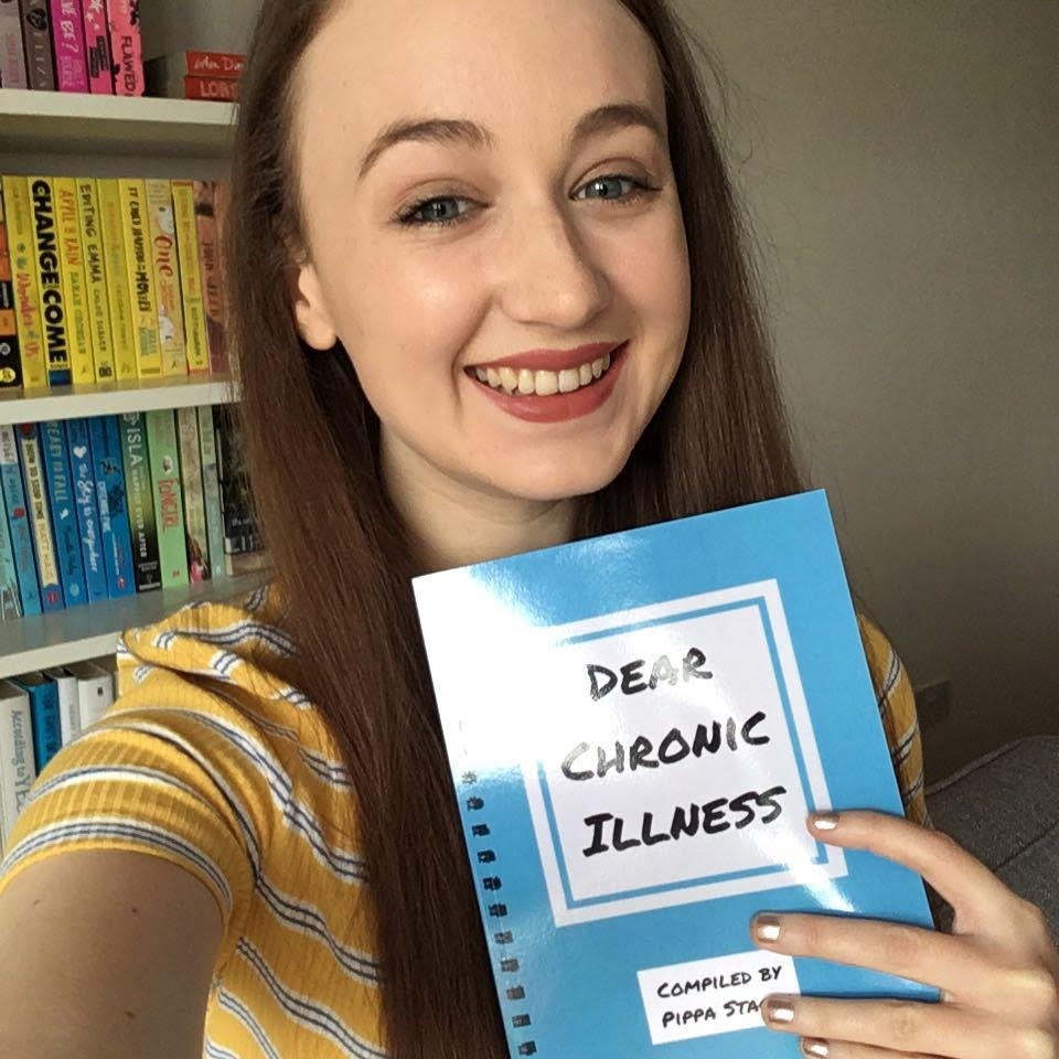 pippa holding up copy of dear chronic illness book, in front of rainbow bookshelves