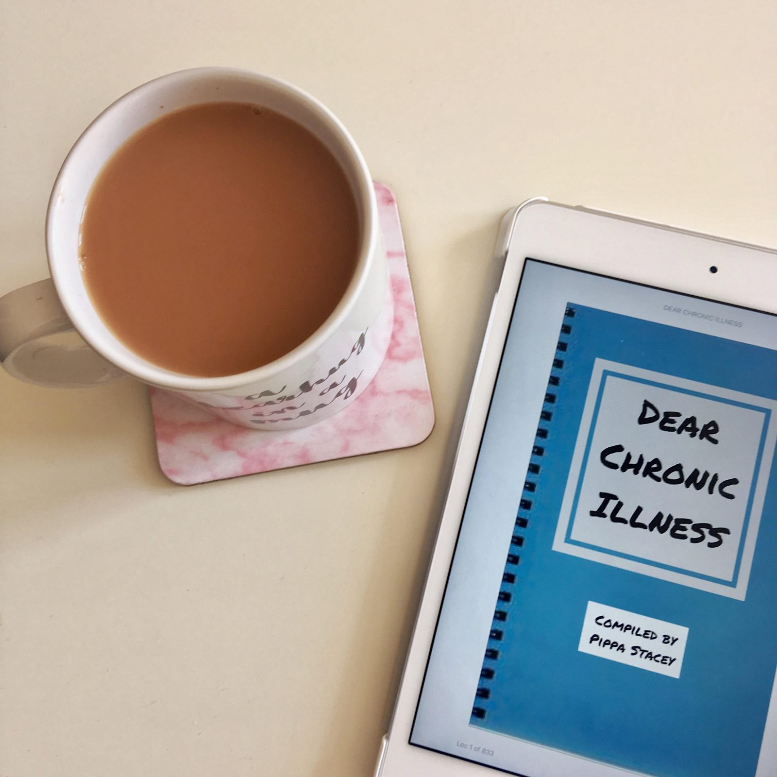 flatlay of cup of tea on pink coaster, next to the 'dear chronic illness' book cover displayed on kindle