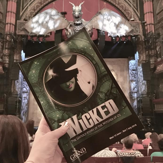 wicked programme (a5) hel up by hand with stage in background