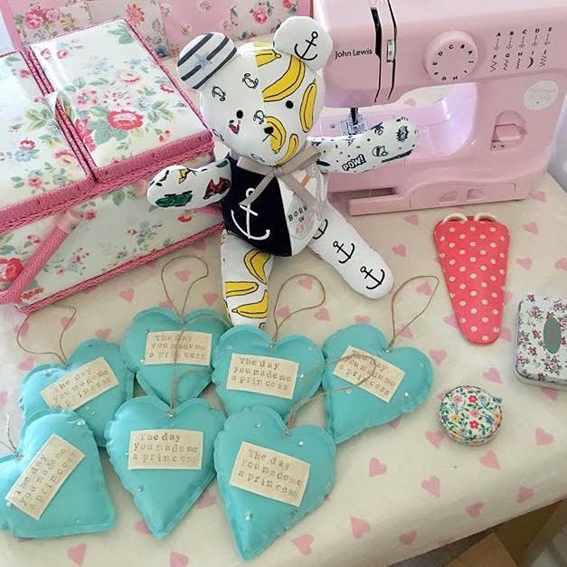 hand sewn teddy and heart decorations with pink sewing machine displayed in background