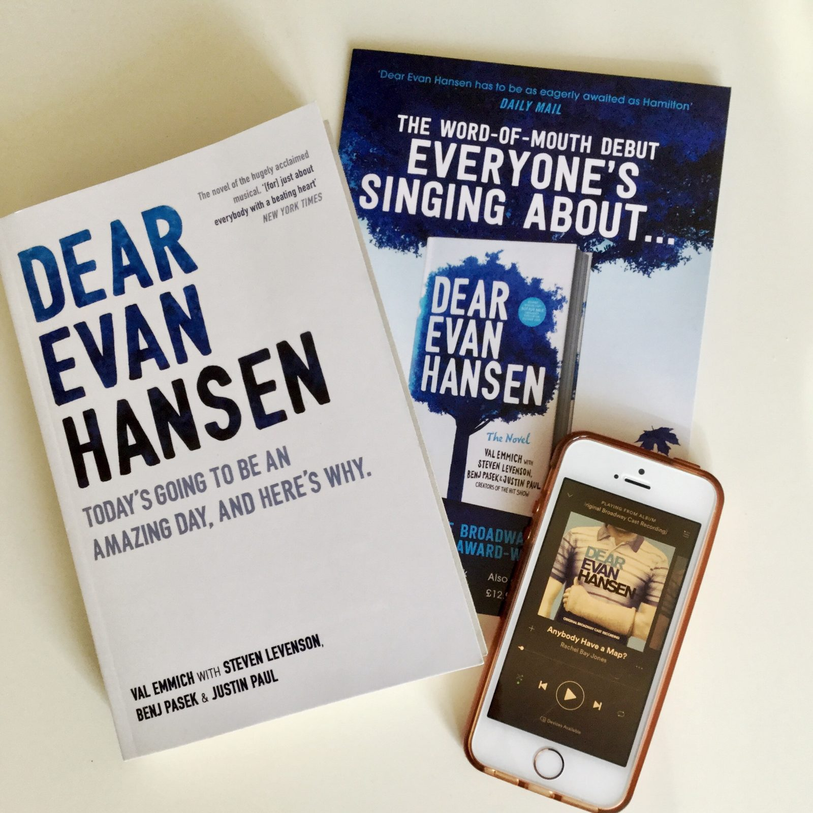 flatlay of dear evan hansen book, leaflet and iphone playing cast recording