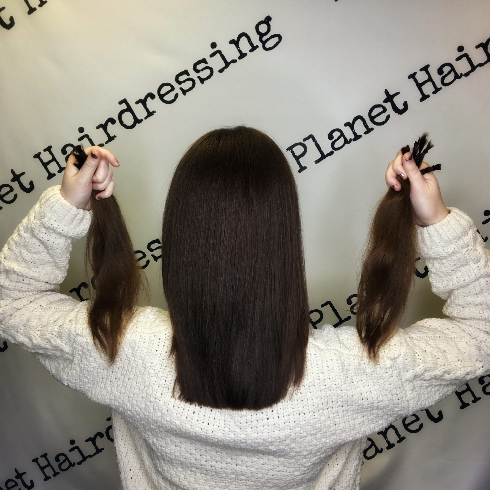 back of pippa's head, holding up two locks of donated hair by each ear