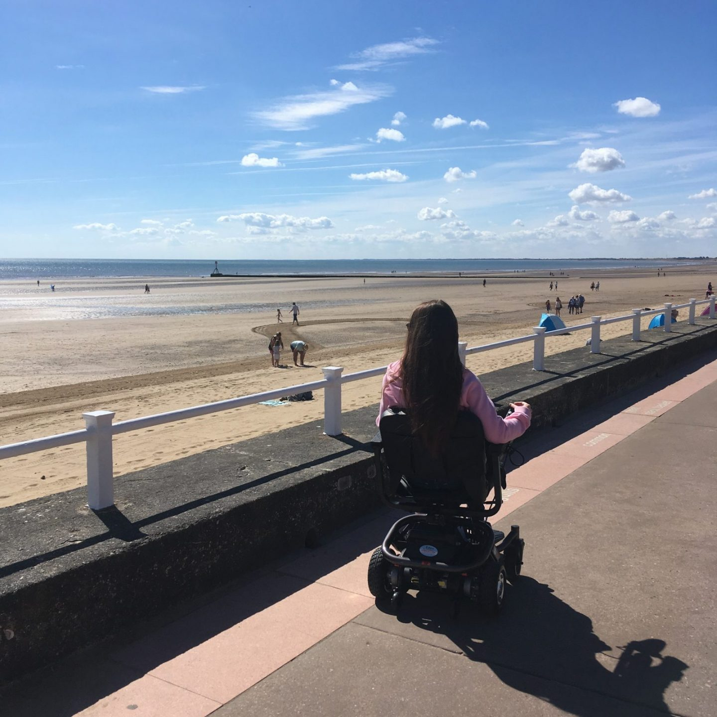 pippa in powerchair with back to camera, wheeling along path next to beach