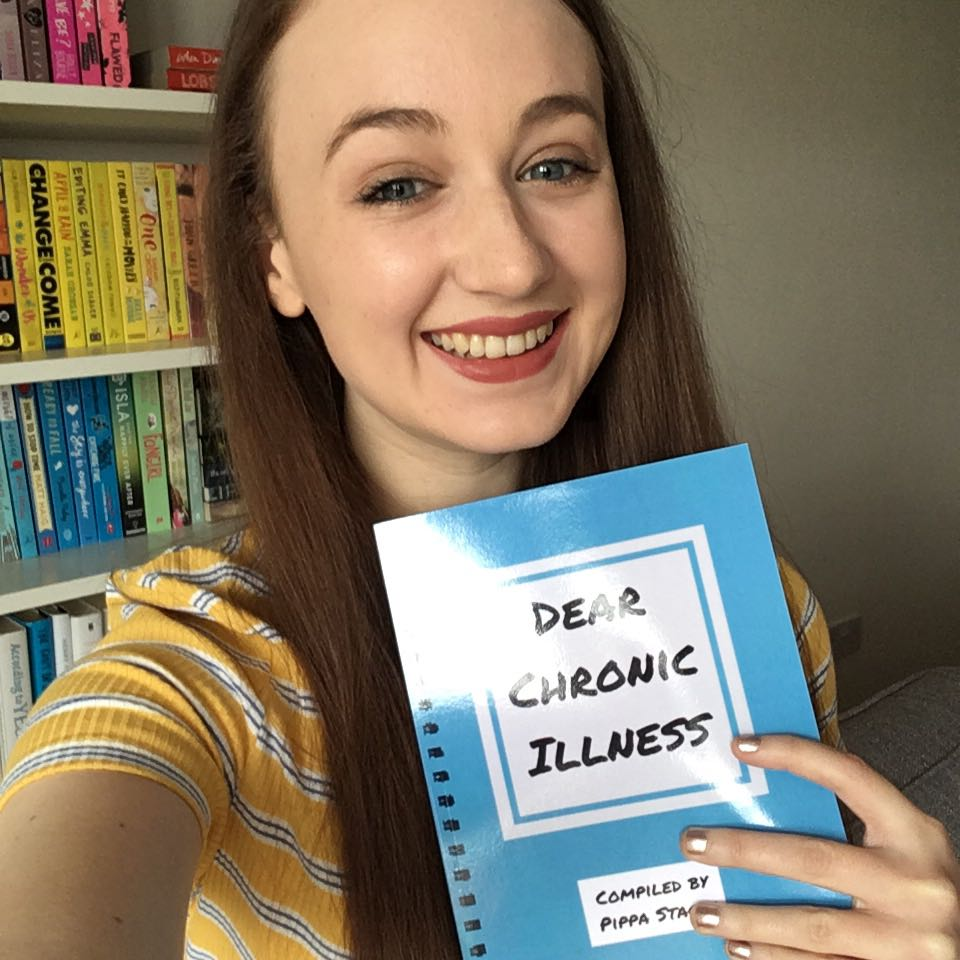 pippa holding up copy of dear chronic illness book and smiling at camera