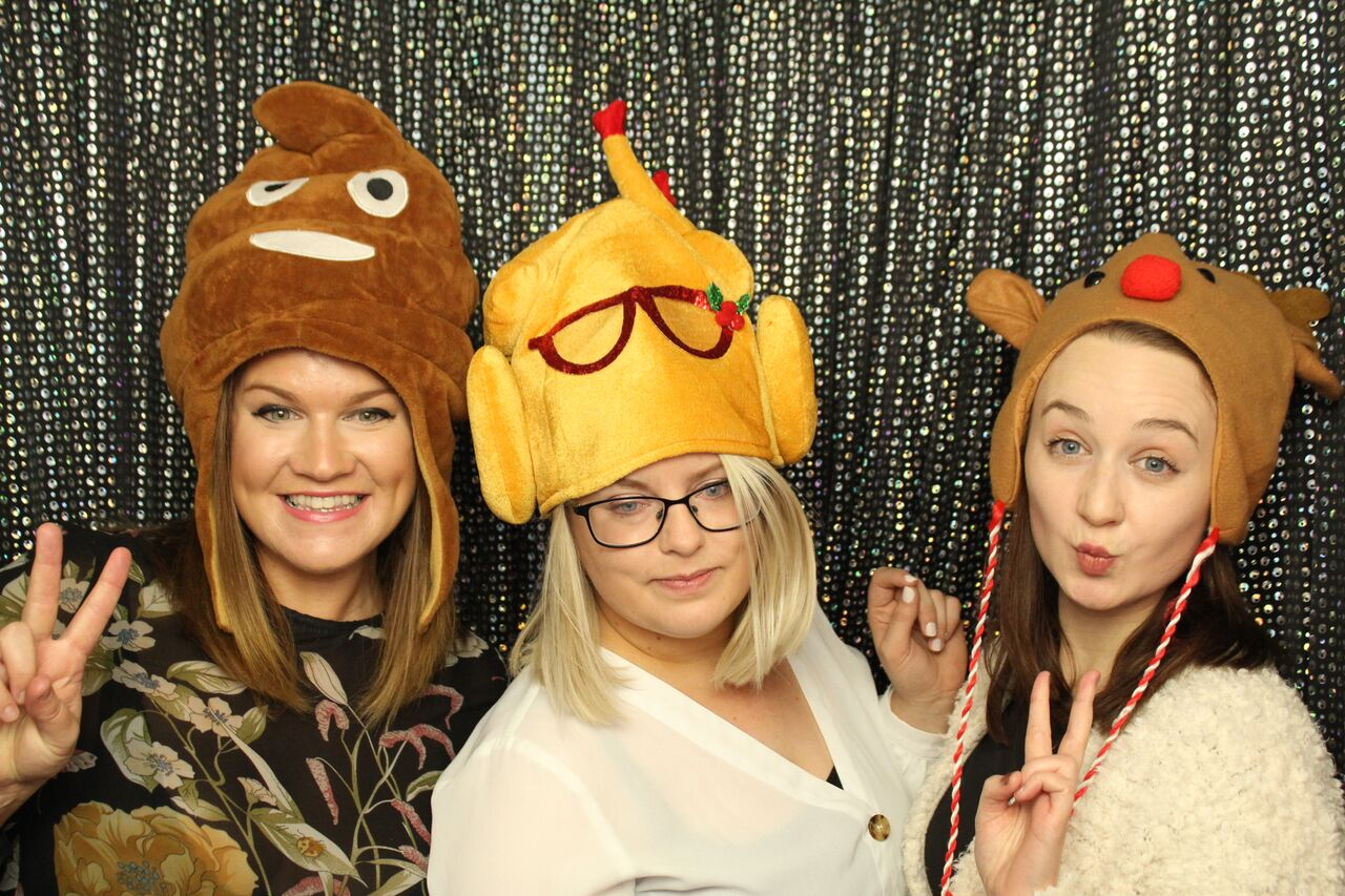 photobooth image of three females wearing silly christmas hats and doing silly poses