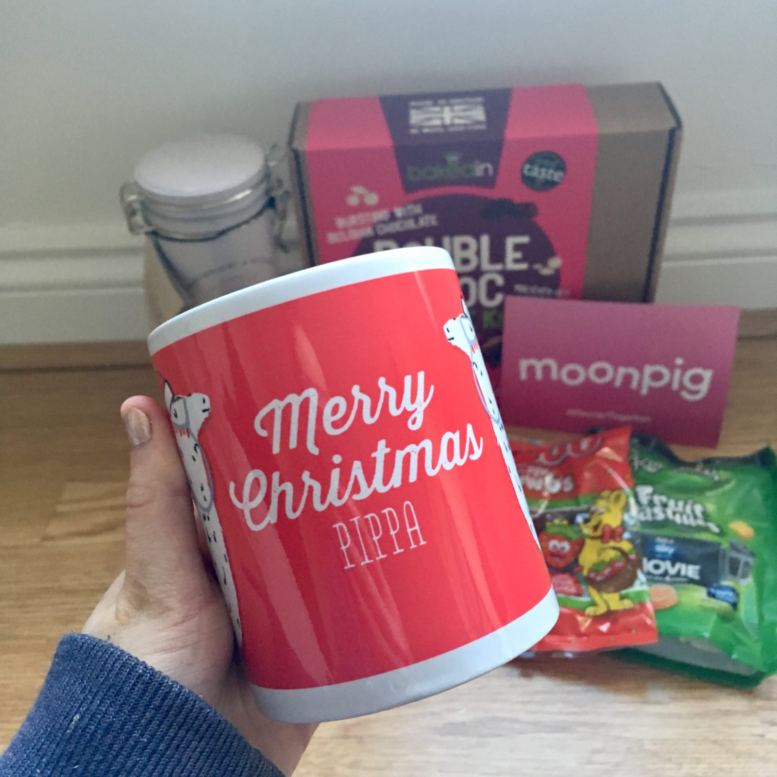 hand holding red christmas mug with other goodie bag items in the background