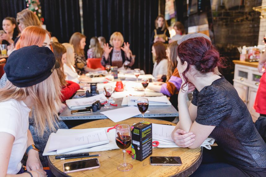 females sat at a long table, looking towards activity leader sat at head of table, gesturing with her hands