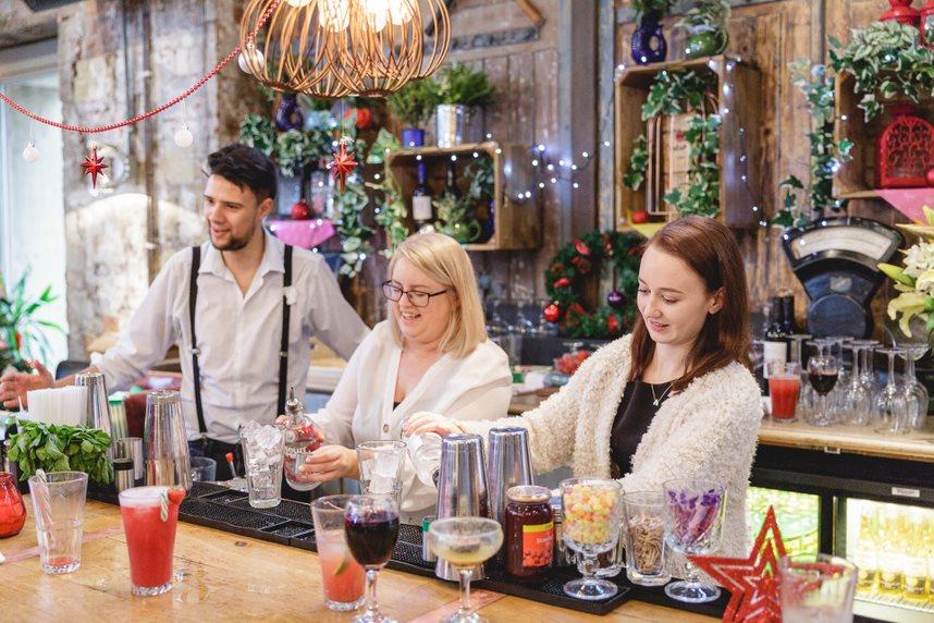 Pippa, Tina and Rev's barman stood behind bar, looking down and mixing cocktails