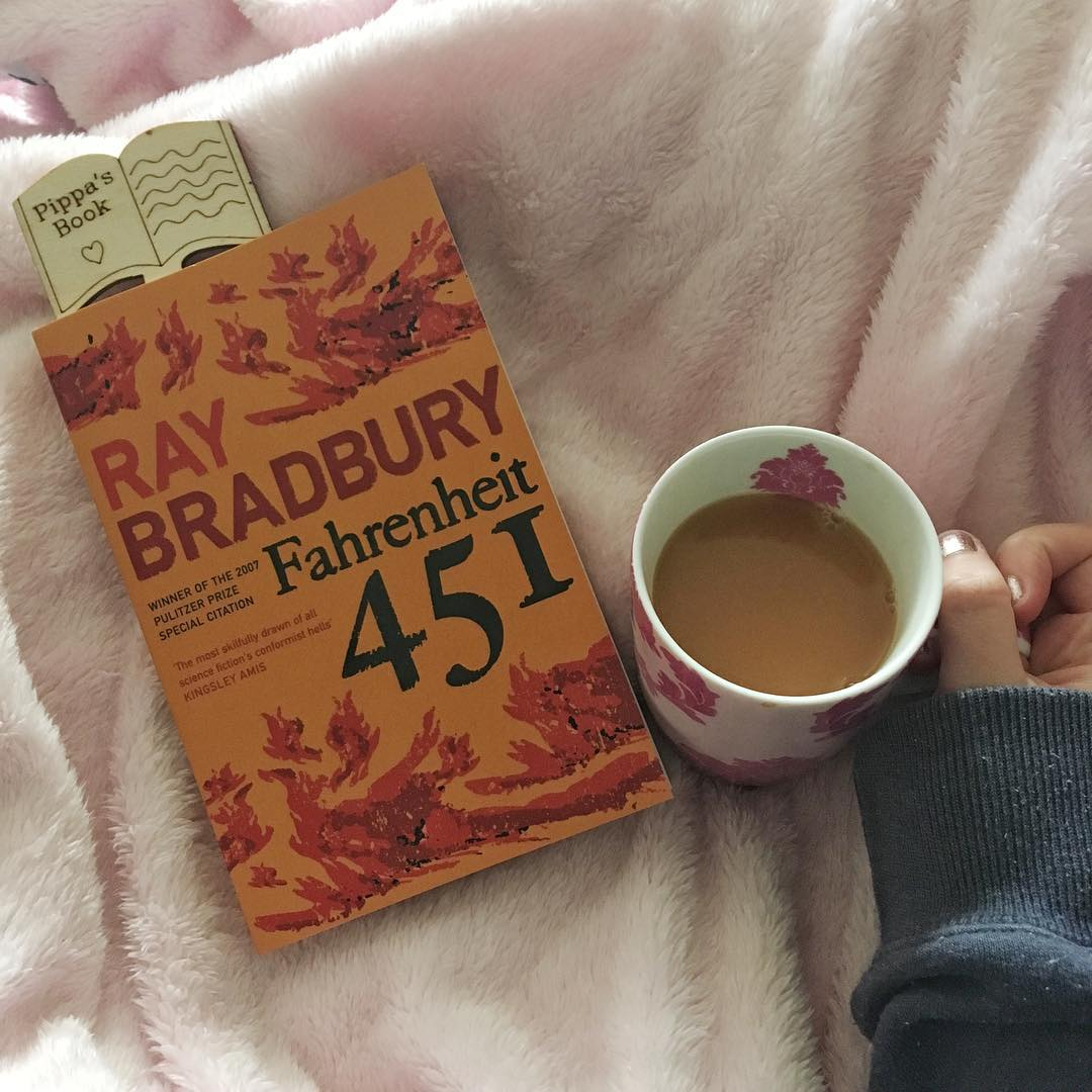 orange cover of fahrenheit 451 by ray bradbury, on top of pink blanket next to hand holding cup of tea in pink mug