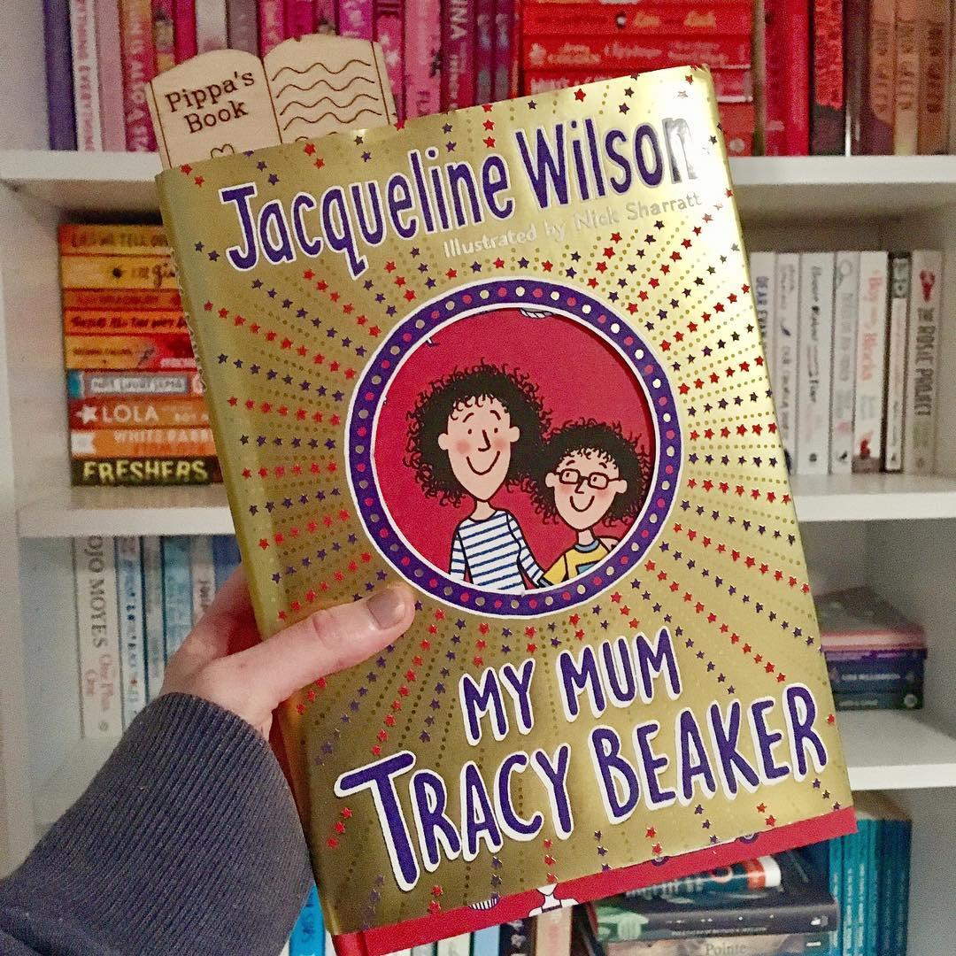 hand holding 'my mum tracy beaker' hardback book in front of rainbow bookshelves