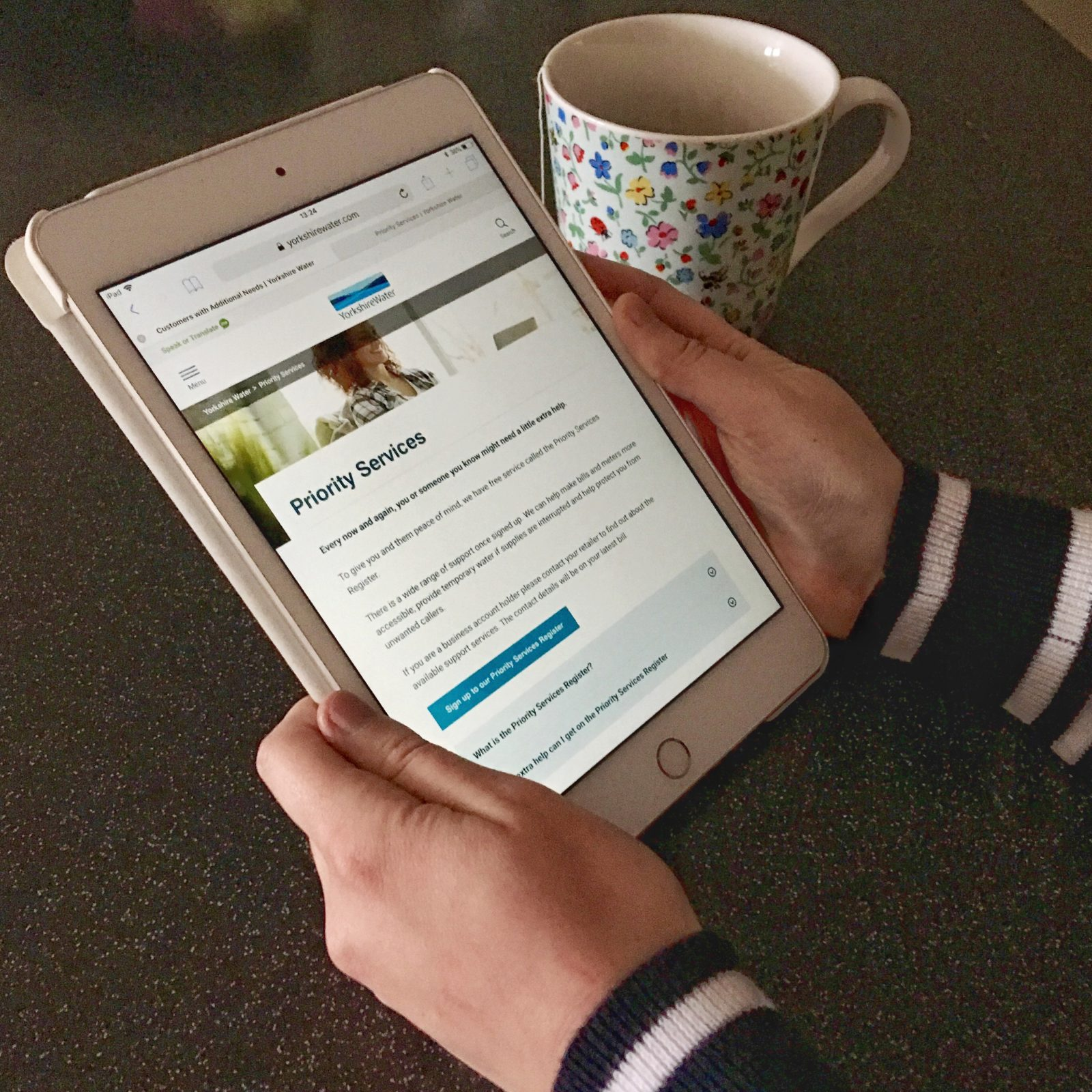 hands holding ipad displaying yorkshire water priority services campaign page, with cup of tea in background