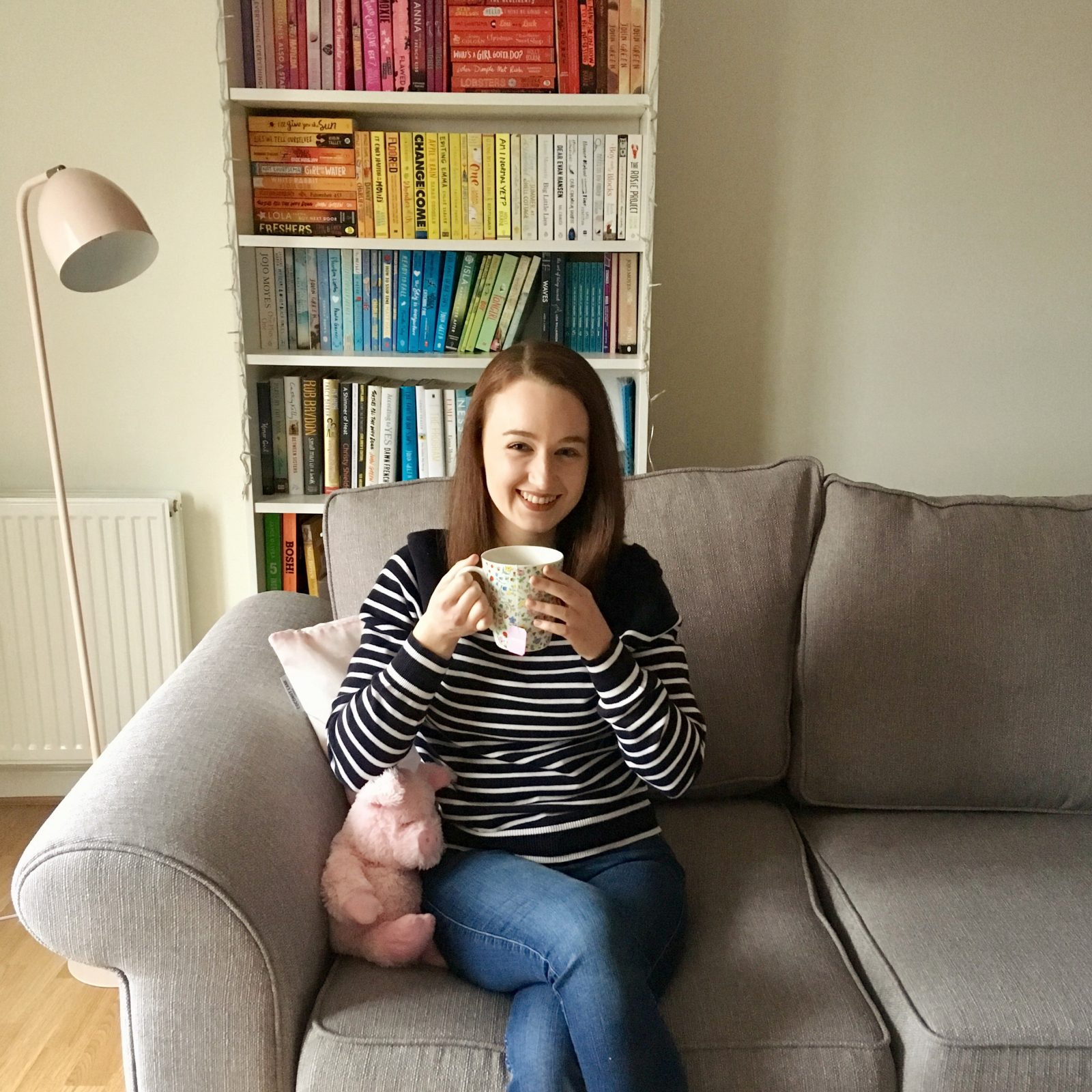 pippa sat on grey sofa holding cup of tea and smiling, with rainbow bookshelves in background