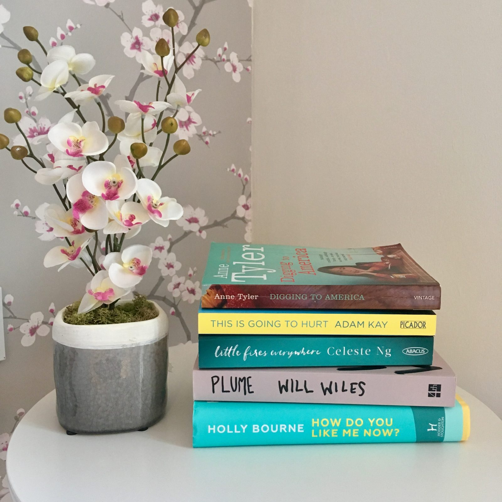 five books stacked on white table next to decorative flowers