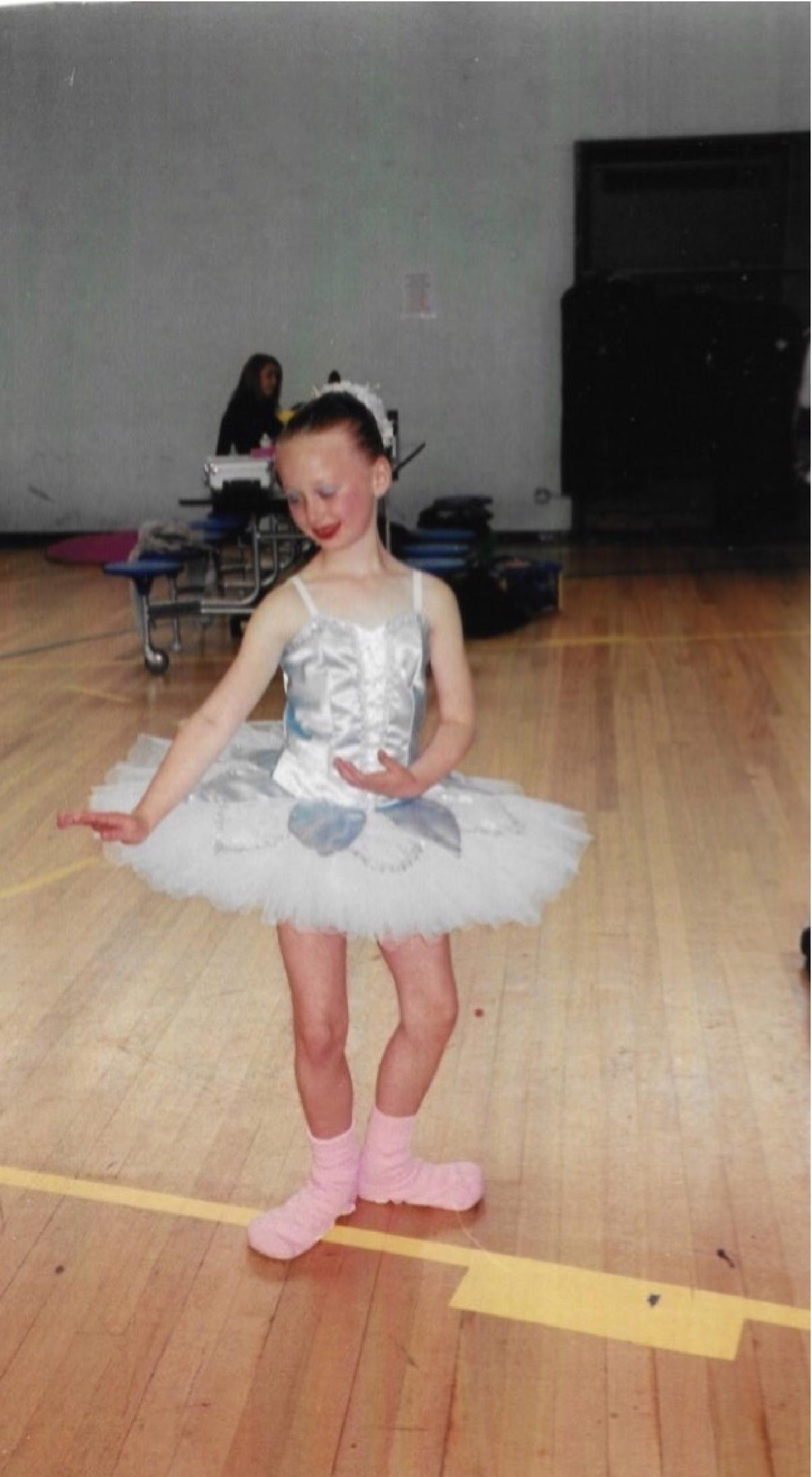 younger pippa backstage dancing, wearing blue tutu and silly pink socks over ballet shoes